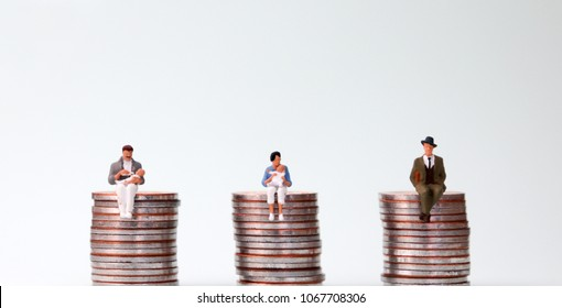 An equal pay concept. Miniature people sitting in the same height pile of coins.
