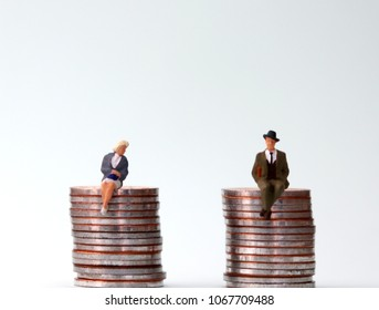 Anequalpayconcept. Miniature people sitting in the same height pile of coins.