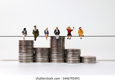 Miniature people sitting side by side with piles of coins of different heights.