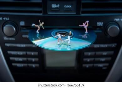 Miniature people skating on CD.