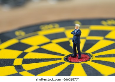 Miniature people small brave confident figure  businessman standing at the center of dartboard as business goal achievement concept.