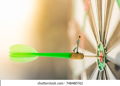 Miniature people: Small business man on red dart arrow hitting in the target center of dartboard with modern city and sunset background. Target business, achieve and victory concept .