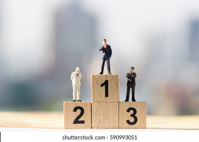 Miniature people: Small businessmen figures standing on wooden podium 1, 2, 3 with cityscape background
