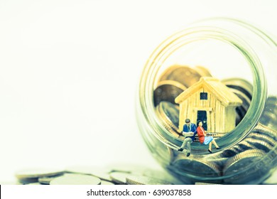 Miniature people: Small couple figure sitting on Piggy bank vase with house and Thai Baht coins. Saving money, property ladder, mortgage and real estate investment concept.