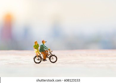 Miniature people : small couple lover figures on bike with vintage world map background. Love and Travel concept.