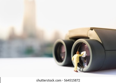 Miniature people: Small figure cleaning binoculars's glasses using as business background.