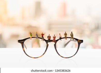 Miniature people : Small figure sitting and wating on glasses. Learning, education and hobby concepts.