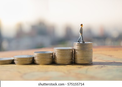 Miniature people: Small figure standing on stack of coin. Money and financial concepts.
