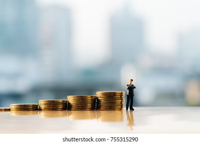 Miniature people: Small figure standing in front of stack of coin. Money and financial concepts.