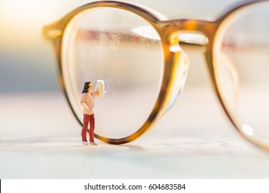 Miniature people : Small figure woman cleaning glasses using as business background.