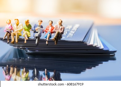 Miniature people: small figures toy Business People sitting and discuss about business deal on stack of credit cards, Banking Finance Technology, Shopping and e-commerce concept