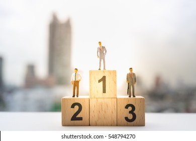 Miniature people: Small worker figures with wooden podium standing on blurred background. Business team competition concept.