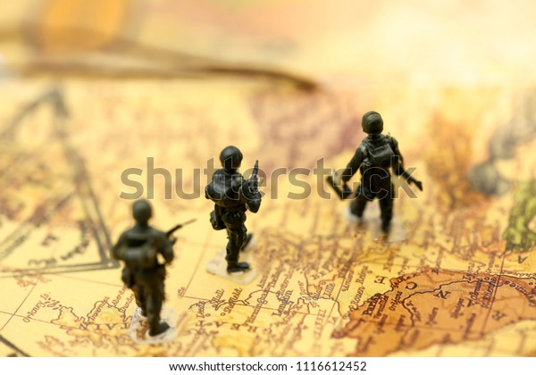 Miniature people : soldiers team with world map,War, army, military, guard concept.