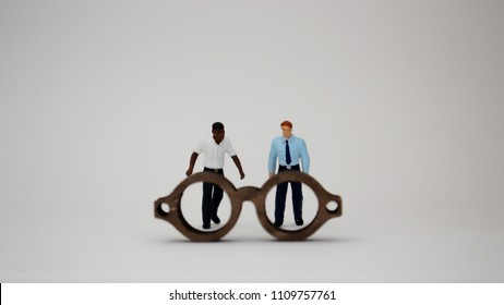 Racist eye concept. Miniature people standing behind wooden miniature glasses.