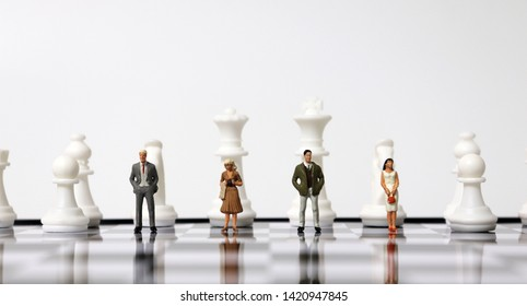 Miniature people standing with chess pieces on the chessboard.