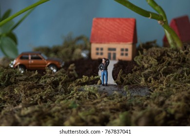 Miniature people standing in front of cute house. New home ownership or concept of pride in your property. First time home owners with their affordable starter home. Rural, working class people.
