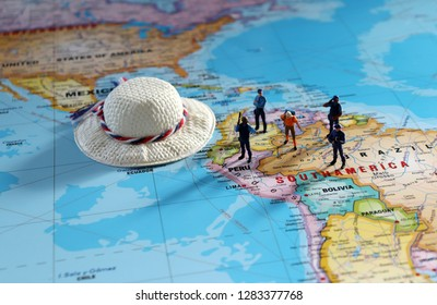 Miniature people standing on a map of the world. A overseas travel safety concept.