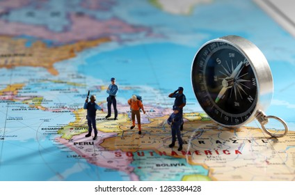Miniature people standing on a map of the world. The concept of emergency in overseas travel.