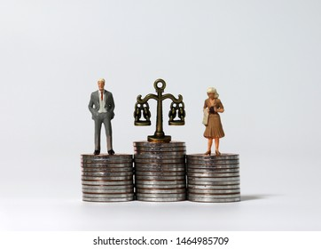 Miniature people standing on a pile of coins of the same height.