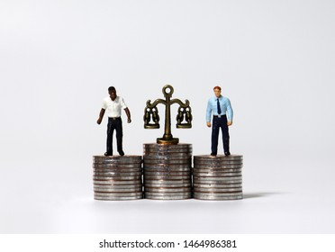 Miniature people standing on a pile of coins of the same height. Pile of coins and a miniature scale.