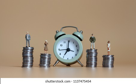 Miniature people standing on top of a pile of coins on both sides of the alarm clock.