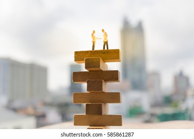 Miniature people: Successive business concept. Businessmen handshaking on top of wood block with modern city background.