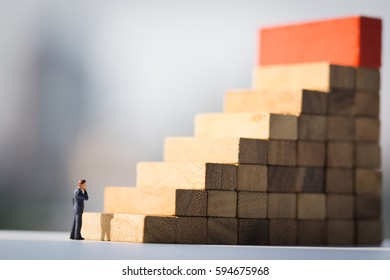 Miniature people: Successive business concept. Businessman thinking on first step of wood stair with modern city background.