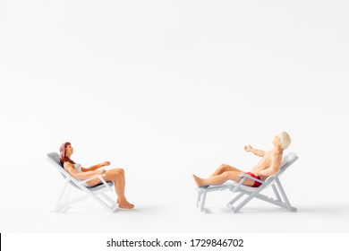 Miniature people sunbathing on deck chairs on white background , Summer time concept