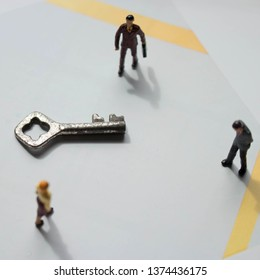 Miniature people surrounding a key.Key to happiness or success concept.Unlock the answer to a problem. Business security team. Minimal background solving a financial problem.Unrecognizable men & women