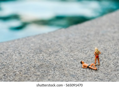 Miniature people in swimsuit relax on the swimming pool floor. Concept of vacation time.