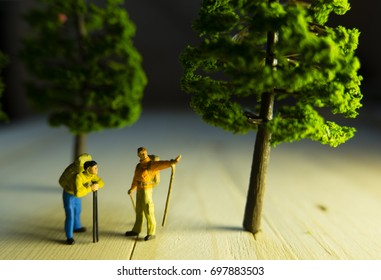 Miniature people toys of travel concept man showing direction with side lighting.