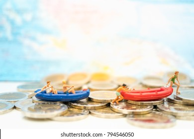 Miniature people: Traveler kayaking on stack of coins with copy space using as background money, finance, travel, business concept.