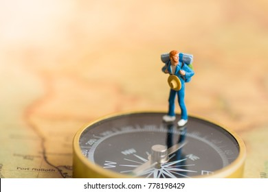 Miniature people : Traveler stand on the compass to tell the direction of travel. Use as a business travel concept.