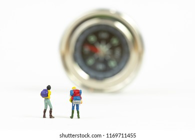 Miniature people travelers mini figures with backpack standing with compass