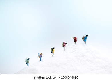 Miniature people: trekkers / climbers climbing snow mountain. Travel and adventure concept