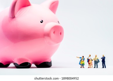 Miniature people. Two adults showing giant piggy bank to a boy