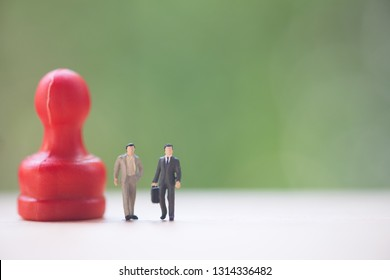 Miniature people: Two businessman standing with red pawn ready for business negotiations