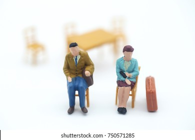 Miniature people of unhappy couple sit a chair with isolated background