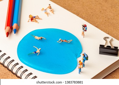 Miniature people: Vacationers are enjoy to swimming in jelly on notebook and office supplies.