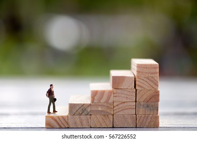 Miniature people walking on stair of wood blocks. Goal concept. think big.
