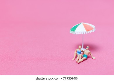 Miniature people wearing swimsuit relaxing on pink background , Valentine's day concept