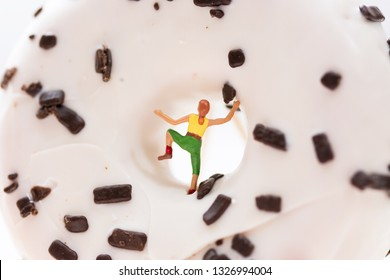 Miniature people, woman climbing a chocholate donut