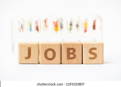 """Miniature people, wooden word block """"JOBS"""" with candidates in capsules as backdrop. Human resource concept, recruiting, hiring process."""