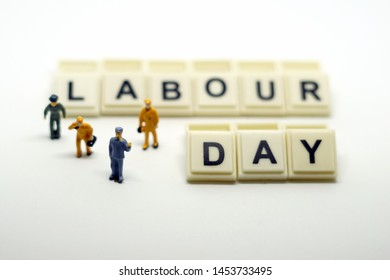 "Miniature people with the word ""Labour Day"" on white background"