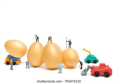 Miniature people work at Easter-eggs for Easter day on white background