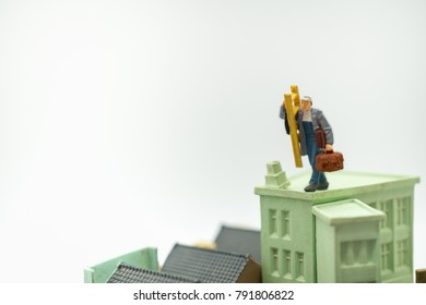 Miniature people: Worker standing on roof with copy space image using as background renovate home service, repair, business concept.