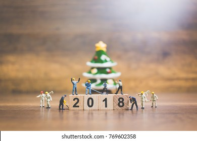 Miniature people : worker team building wooden block number 2018 on wooden background, Christmas celebration concept.