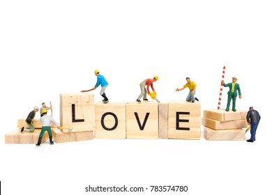 """Miniature people : Worker team building word """" Love """" on wooden block with white background , Valentine's day concept"""