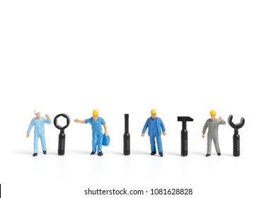 Miniature people : Worker team with tools supplies on white background , construction concept