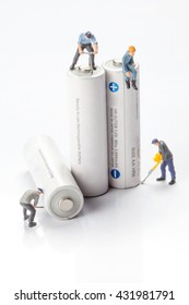 miniature people  - workers moving and recycle batteries,  isolated on white